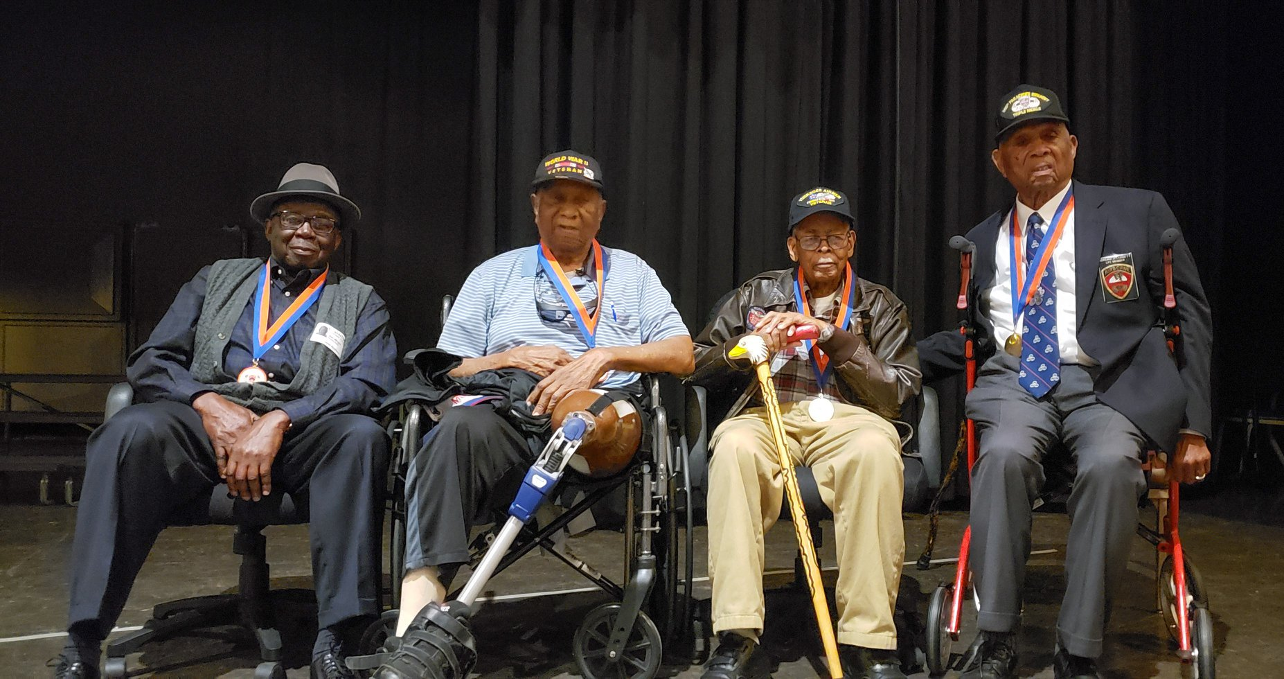 Four Former African American members sitting on a high school stage.