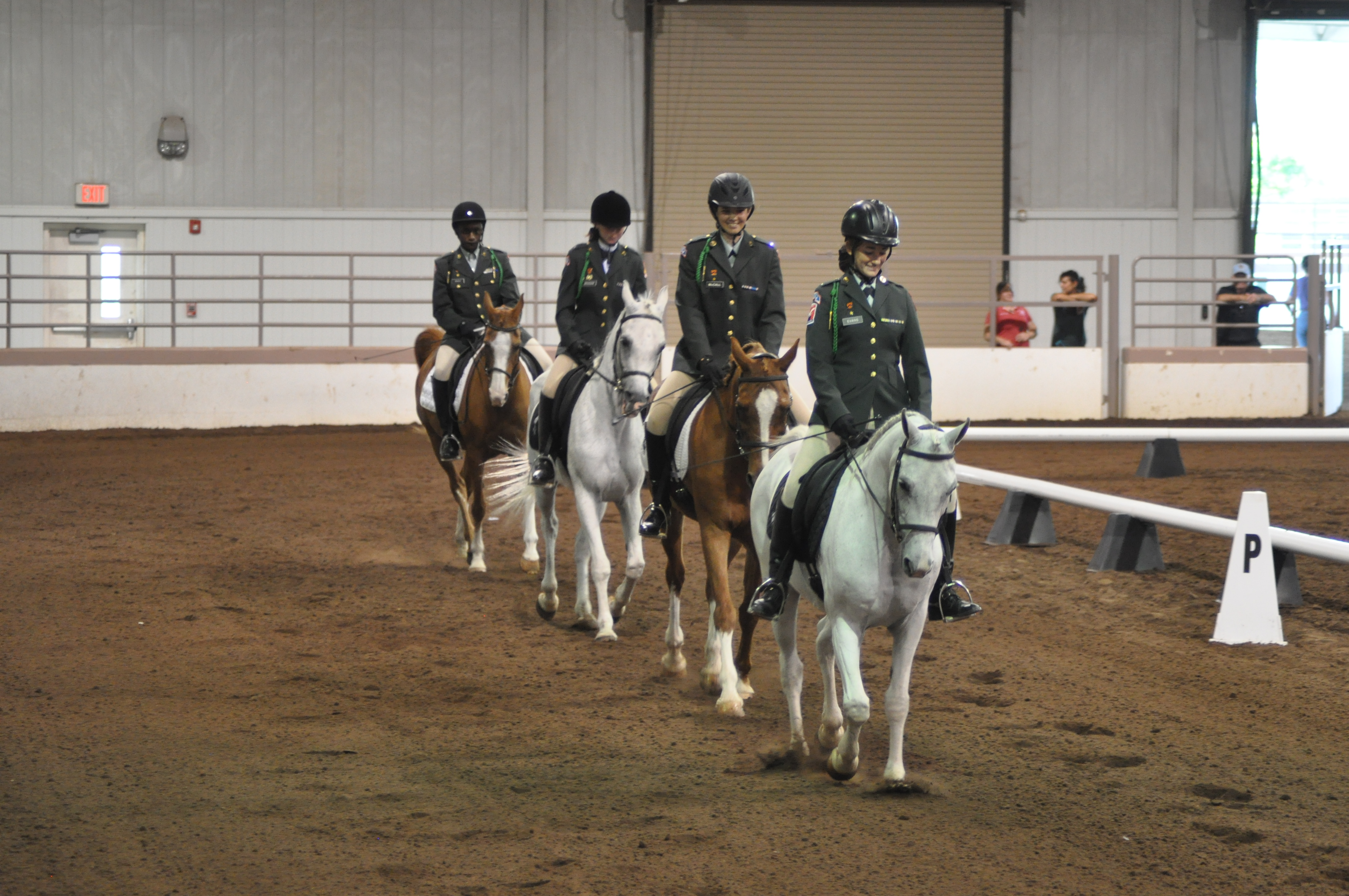 Four students riding horses in an equestrian competition.