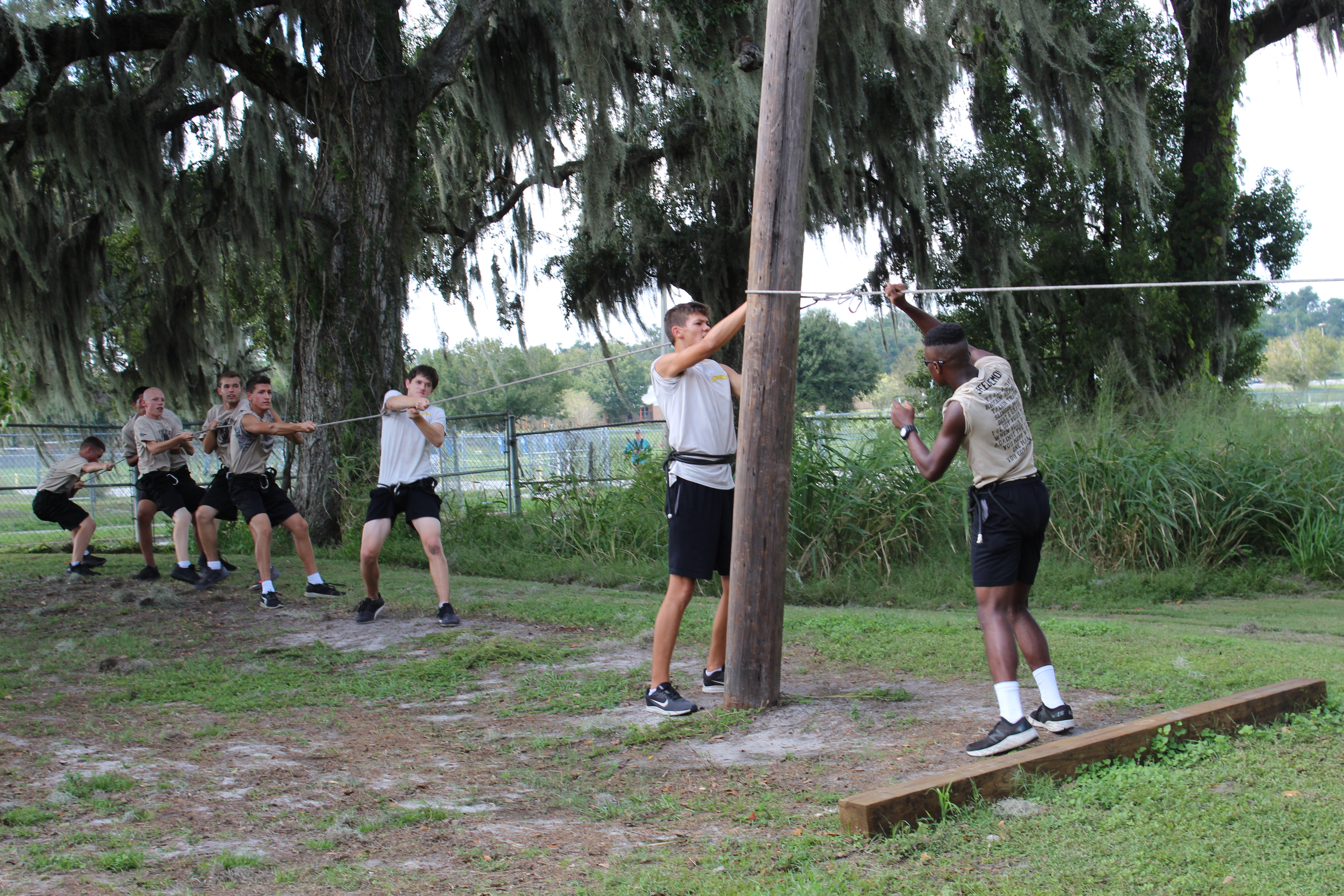 Students working on tying a suspension rope to a wooden pole during a competitive drill.