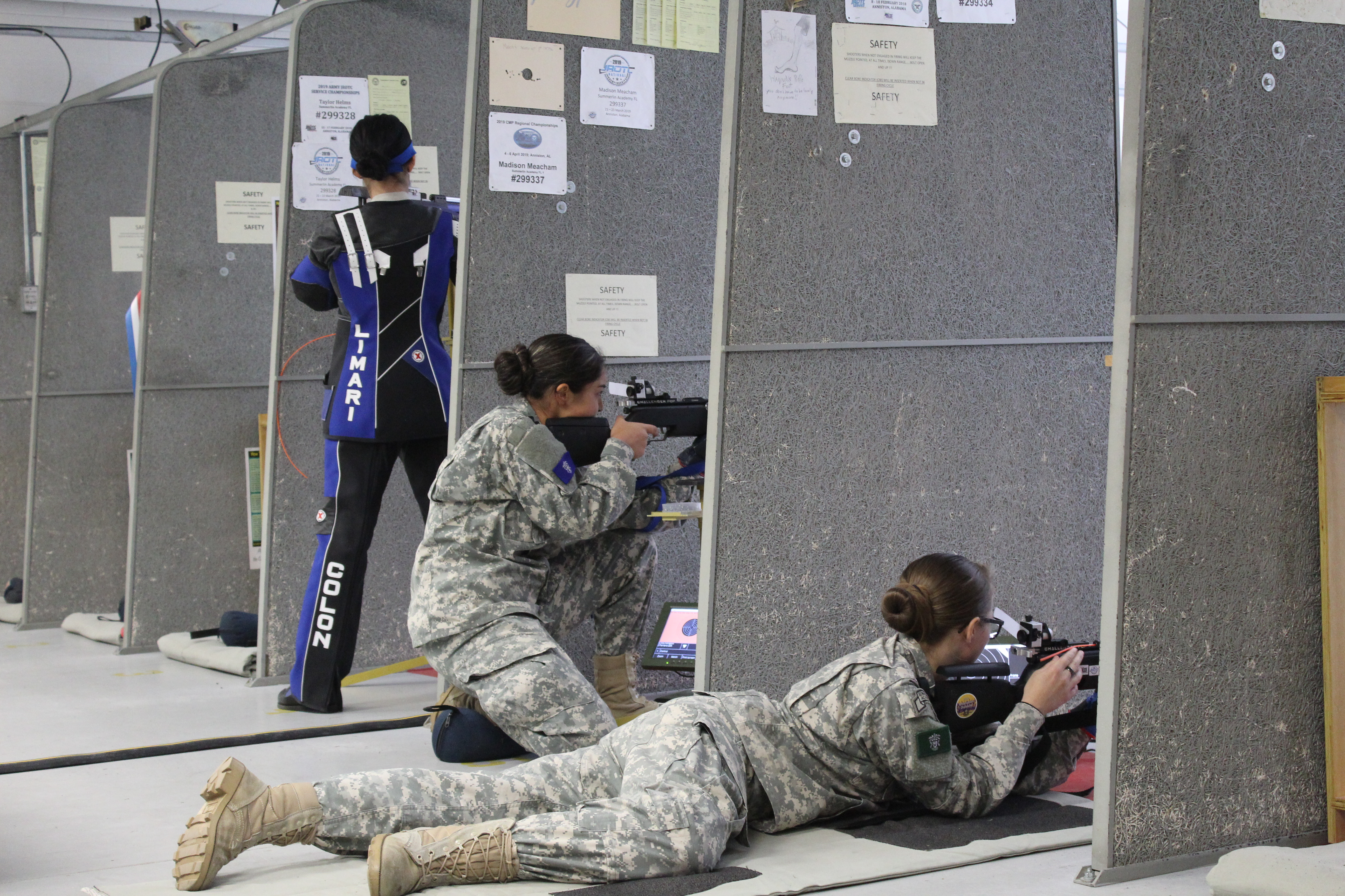 Three students practicing rifle shooting in an indoor shooting range.