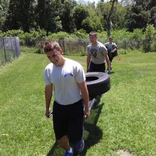 Students at Summerlin Academy carrying a tire during a PT exercise.