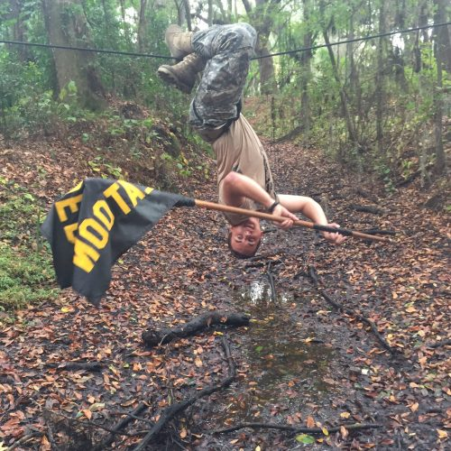 Student hanging upside down holding a flag over a muddy creek.