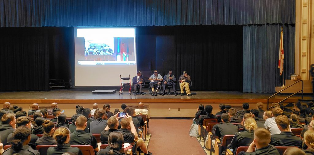 Four African American men sitting on stage during an event at high school.